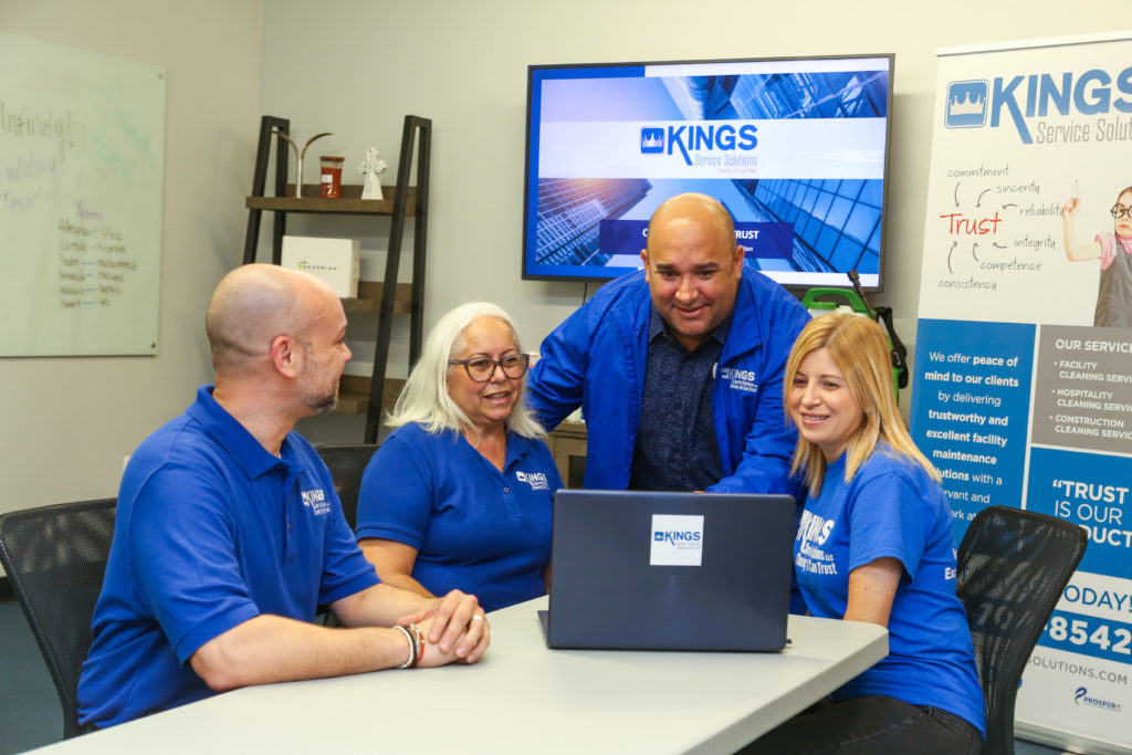 Four employees in front of a computer